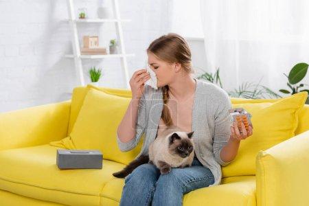 Photo pour Femme allergique tenant des pilules et serviette près de chat siamois poilu sur canapé jaune - image libre de droit