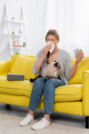 Woman with allergy sneezing while holding pills and siamese cat