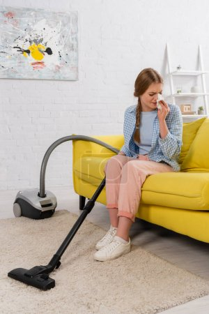 Photo for Young woman holding napkin during allergy reaction on dust near vacuum cleaner - Royalty Free Image