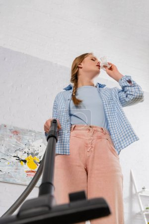 Low angle view of woman with allergy on dust holding brush of vacuum cleaner on blurred foreground