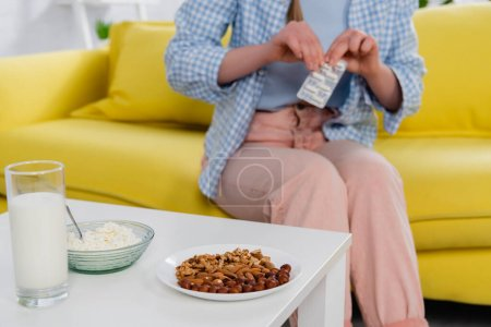 Cropped view of nuts, cottage cheese and milk on table near woman with allergy holding pills on blurred background
