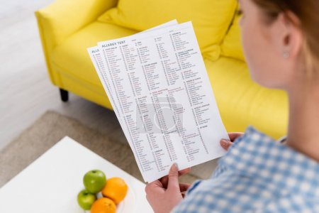 Papers with allergy test results in hands of woman on blurred foreground