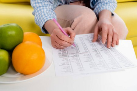 Cropped view of woman holding pen near allergy test results near fresh fruits