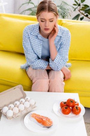 Photo pour Saumon, oeufs et tomates près de femme allergique sur canapé - image libre de droit