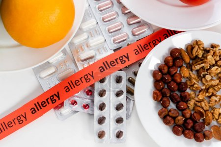 Photo pour Top view of ribbon with allergy lettering, pills and nuts on table - image libre de droit