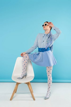glamour woman stepping on chair while posing with hand near head on blue background