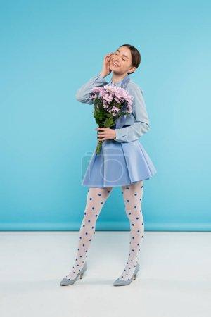 Photo pour Heureuse femme élégante tenant chrysanthèmes roses tout en se tenant les yeux fermés sur fond bleu - image libre de droit