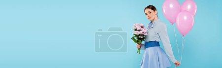 Photo pour Femme à la mode regardant la caméra tout en posant avec des ballons roses et des fleurs isolées sur bleu, bannière - image libre de droit