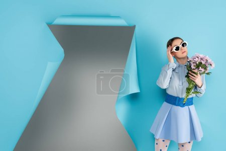 Photo for Fashionable woman in eyeglasses holding flowers near hole in blue paper with grey background - Royalty Free Image