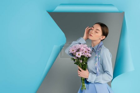 Photo for Elegant woman touching face while posing with closed eyes and pink flowers near blue torn paper on grey background - Royalty Free Image
