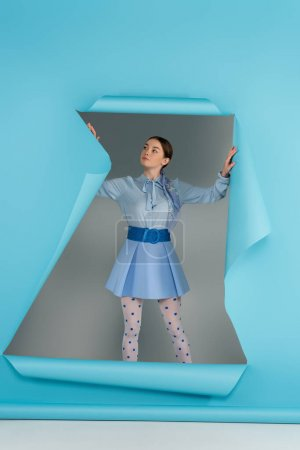 glamour woman in dotted tights standing near hole in blue paper on grey background