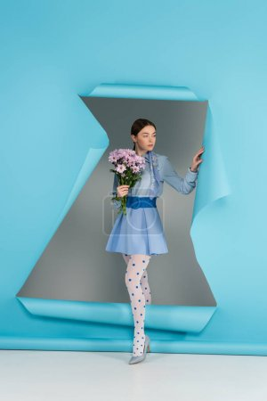 Photo for Trendy woman in dotted tights standing with pink flowers near hole in blue paper on grey background - Royalty Free Image