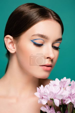 portrait of young sensual woman with creative makeup posing near pink flowers isolated on green