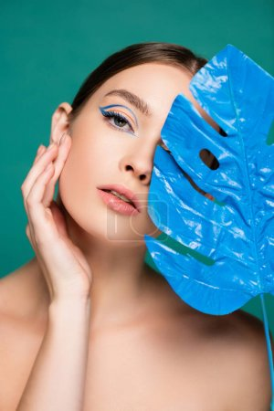 charming woman touching face while looking at camera near blue wet leaf isolated on green