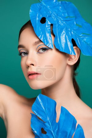 sensual woman with creative makeup looking at camera near blue shiny leaves isolated on green