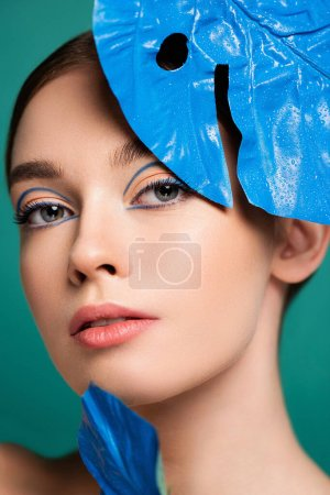portrait of charming woman near blue glossy leaf isolated on green