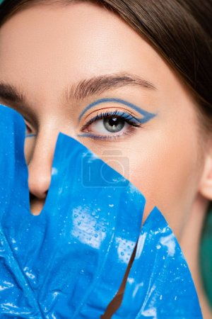 close up view of woman with creative makeup obscuring face with blue leaf