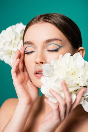 Photo for Charming woman with blue eyeliner on closed eyes posing with white peonies isolated on green - Royalty Free Image
