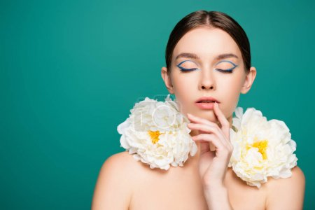 sensual woman with closed eyes and white peonies on shoulders touching lips isolated on green