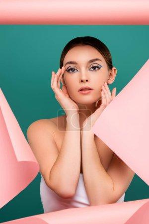junge Frau mit kreativem Make-up berührt Gesicht nahe Loch in rosa Papier isoliert auf grün