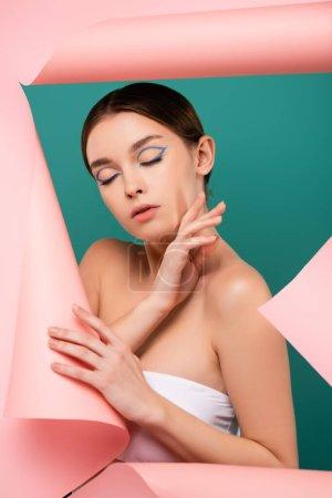 Photo pour Jeune femme avec les yeux fermés touchant le visage près du trou dans du papier rose isolé sur vert - image libre de droit