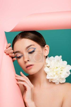 mujer joven con maquillaje creativo y peonía flor en el hombro cerca de rosa rasgado papel aislado en verde