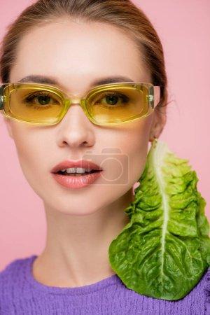 Nahaufnahme Porträt einer Frau mit farbigen Brillen und frischem Kopfsalat-Ohrring isoliert auf rosa