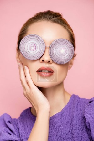 young woman touching face while posing in eyeglasses with onion rings isolated on pink, surrealism concept
