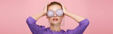 woman in eyeglasses with onion rings, touching head while posing isolated on pink, banner