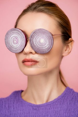close up view of woman with onion rings eyeglasses isolated on pink, surrealism concept