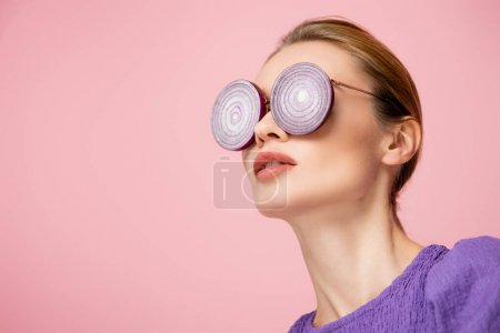 young woman posing in eyeglasses with purple onion rings isolated on pink, surrealism concept