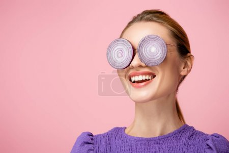 smiling woman wearing eyeglasses with purple onion rings isolated on pink, surrealism concept