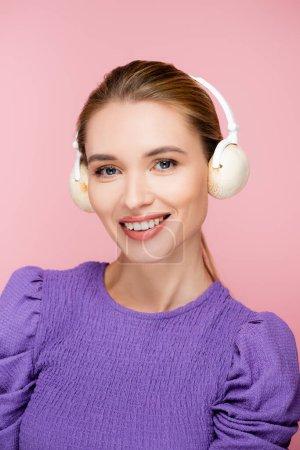 fröhliche Frau mit Pilzen im Kopfhörer, die vereinzelt in die Kamera auf rosa schaut