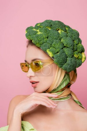 Photo pour Charmante femme aux lunettes colorées, posant dans un chapeau en brocoli isolé sur rose, concept surréaliste - image libre de droit