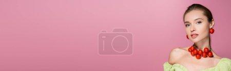Charmante Frau mit Halskette und Ohrringen aus Kirschtomaten isoliert auf rosa, Banner