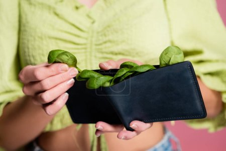 partial view of woman holding wallet with fresh green spinach, selective focus