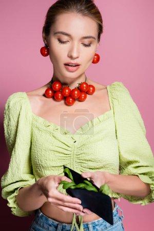 Photo pour Jeune femme en cerise tomates collier, tenant portefeuille avec des épinards sur rose - image libre de droit