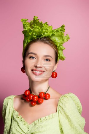 happy woman in necklace, earrings and hat made of vegetables smiling at camera on pink