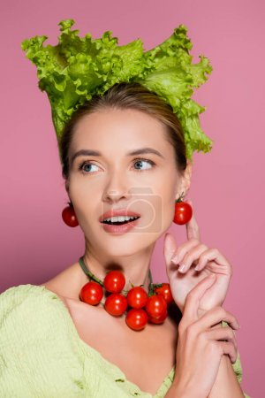pretty woman in lettuce hat, and earrings made of cherry tomatoes on pink