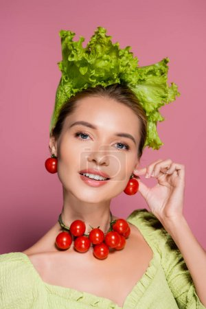 smiling woman in hat, necklace and earrings made of fresh vegetables posing on pink