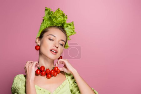 charming woman in lettuce hat, touching necklace mad of cheery tomatoes on pink
