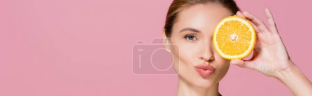 Photo for Charming woman sending air kiss while holding half of ripe orange isolated on pink, banner - Royalty Free Image
