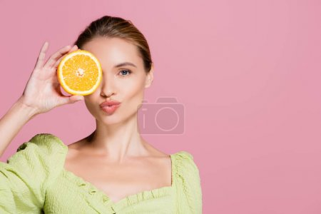 sensual woman covering eye with half of juicy orange and sending air kiss isolated on pink