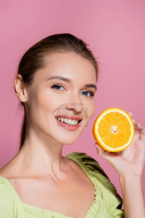 charming woman with natural makeup holding half of ripe orange isolated on pink