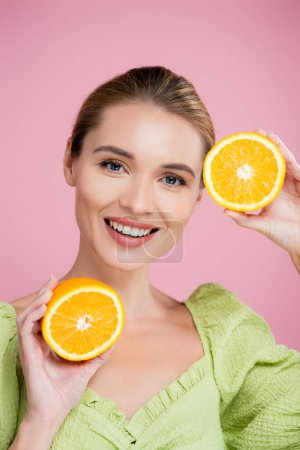 Photo for Joyful woman with halves of ripe orange smiling at camera isolated on pink - Royalty Free Image