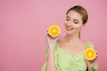 joyful woman in green blouse holding halves of ripe juicy orange isolated on pink