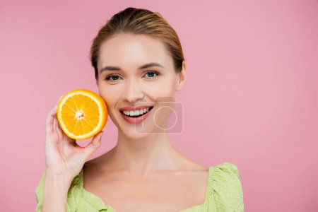 Photo for Young smiling woman holding half of ripe juicy orange isolated on pink - Royalty Free Image