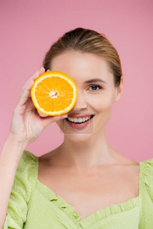 cheerful woman covering eye with half of juicy orange isolated on pink