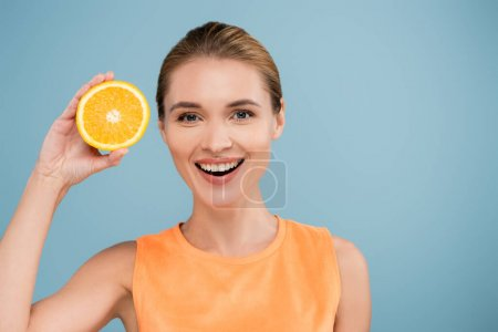 joyful woman smiling at camera while holding half of juicy orange isolated on blue