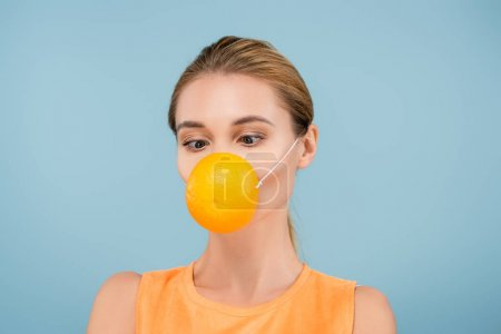 young woman in safety mask made of orange half isolated on blue